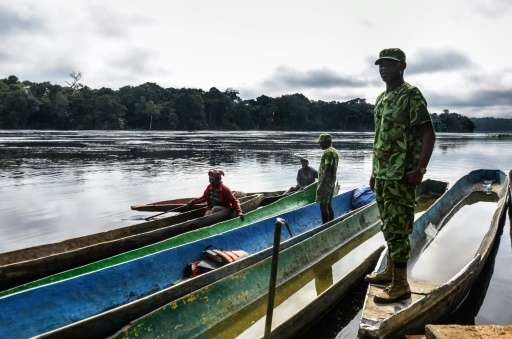 Rangers stop pirogues to check for arms and ammunition, on a stretch of the Ivindo river in the Ivindo National Park, Gabon