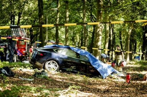 Rescue workers proceed with caution around the spot where a Tesla slammed into a tree in Baarn, on September 7, 2016