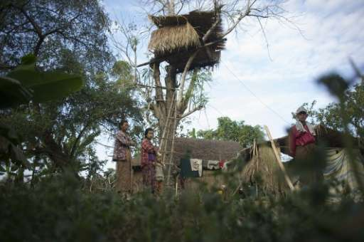 Residents stand near a tree house in the Kyauk Ye village on the outskirts of Yangon on January 14, 2016