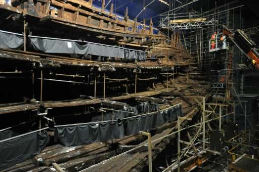 Restoration staff work on part of the hull of the Tudor the warship Mary Rose during a press preview of the new Mary Rose Museum