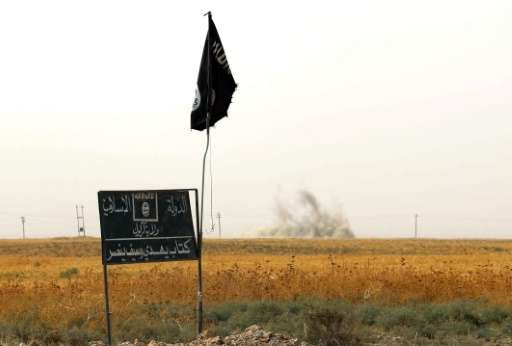Smoke rises in the distance behind an Islamic State group (IS) flag and banner on September 11, 2015