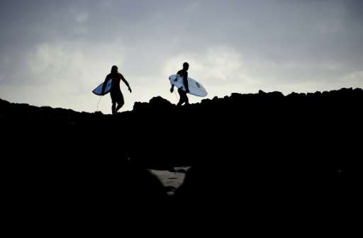 Surfers make their way over rocks to surf in Ballina, the Australian town now infamous for a  spate of shark attacks