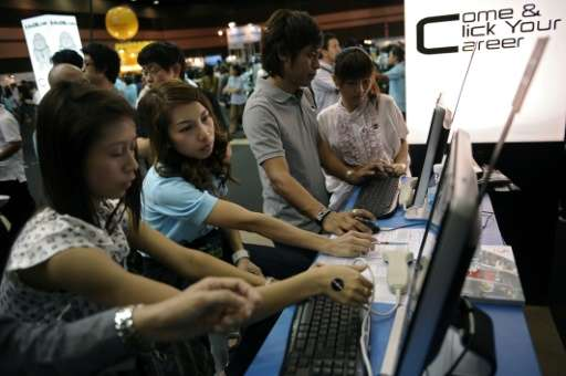 Thai workers look at job advertisements in Bangkok