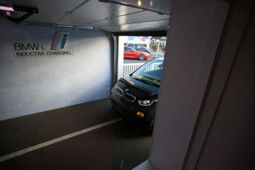 This photo taken on January 8, 2016 shows a BMW i3 electric car as it drives autonomously into a simulated garage to park over a