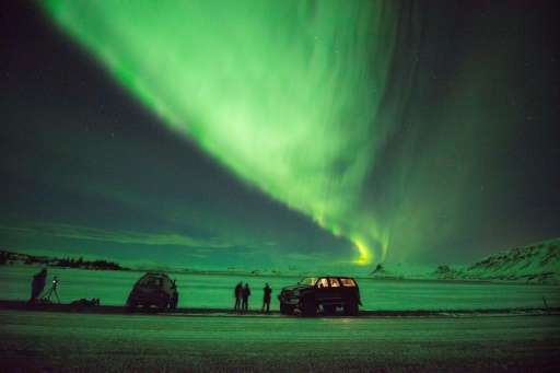 Tourists photograph the Northern Lights at Lake Thingvellir, Iceland
