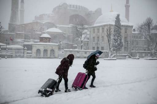 Tourists pull their luggage through snow in the Hagia Sofia district in Istanbul on December 31, 2015