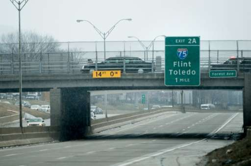 US President Barack Obama's limousine drives past a sign for Flint, Michigan as he travels to a lunch on January 20, 2016 in Det