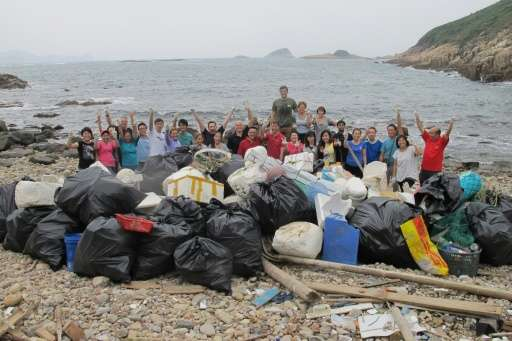 Volunteers pose with all the rubbish collected and bagged for removal at a beach in Hong Kong