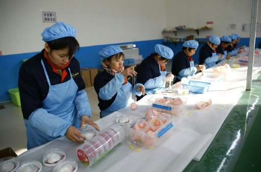 Women work on a pollution mask assembly line at the ASL Masks factory in Dongliu, China's Shandong province