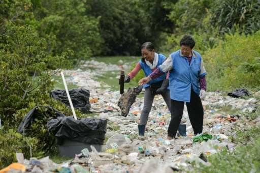 Workers clean up refuse washed ashore at the top of a beach in Hong Kong on July 10, 2016