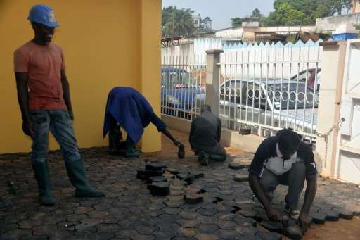 Workers pave the ground with recycled cobblestones made of plastic waste, in Yaounde, Cameroon