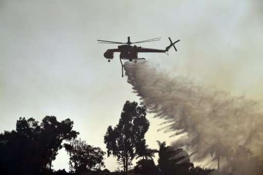 A helicopter drops water on the Skirball Fire in west Los Angeles, California