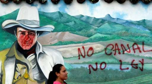 "A woman is seen in front of a wall with a graffiti reading ""No canal, no law"" during a protest against the constructio"