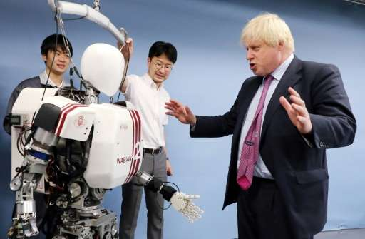 Britain's Foreign Secretary Boris Johnson (R) looks at the humanoid robot Wabian II, which resembles a tiny astronaut that Wased