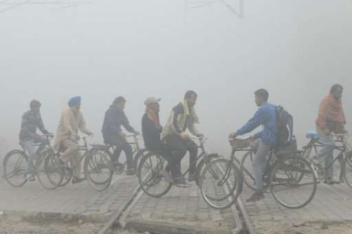 Indian commuters ride over tracks at a railway crossing amid heavy smog in Amritsar