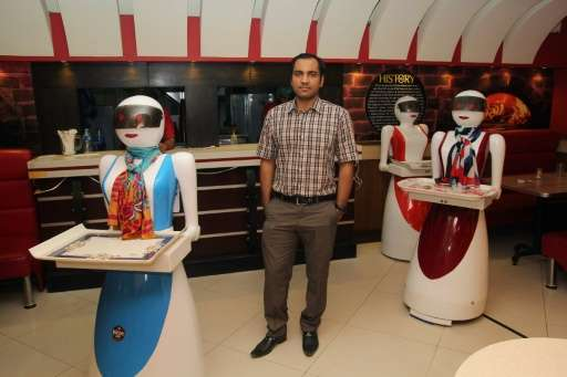 In this photograph taken on July 4, 2017, Pakistani engineer Osama Jafari (C) poses with robot waitresses Annie (L), Rabia (R) a