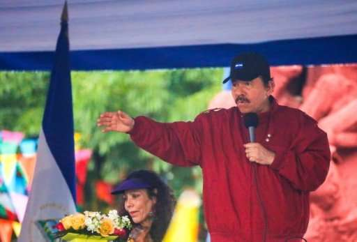 Nicaraguan President Daniel Ortega (R), flanked by his wife and Vice President Rosario Murillo (L), speaks to supporters in Mana