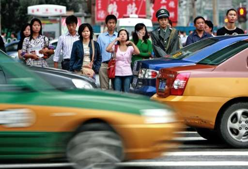 Pedestrians wait for the light to change in  Beijing, but people not obeying the rules of the road in other parts of China might
