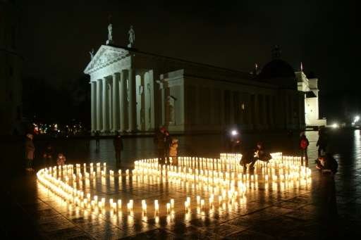 People attend a candle light vigil at the Vilnius Cathedral as it stands unlit during Earth Hour