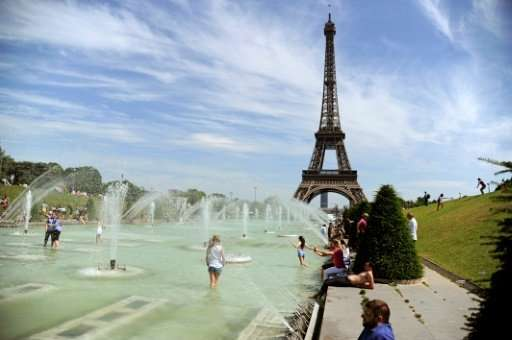 People refresh themselves in the fountain of the Trocadero Gardens by the Eiffel Tower during a June 2015 heatwave in Paris, whe