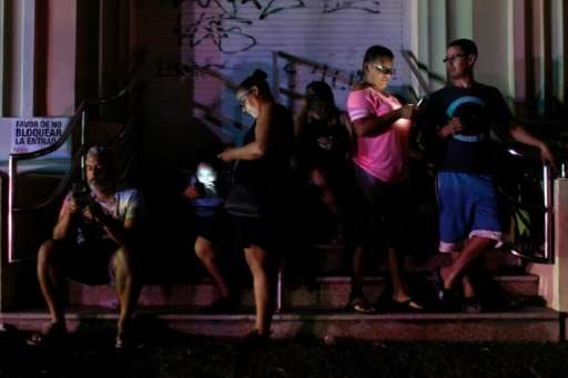 People use their cell phones in one of the few places with signal in San Juan, Puerto Rico. 83 per cent of cell sites were still