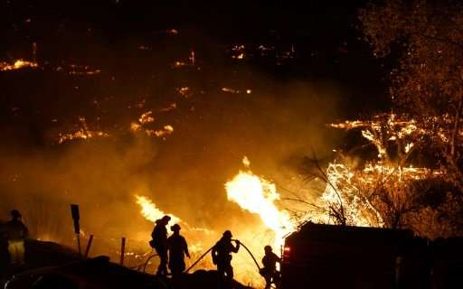 Firefighters battle the Lilac fire in Bonsall, California on December 7, 2017