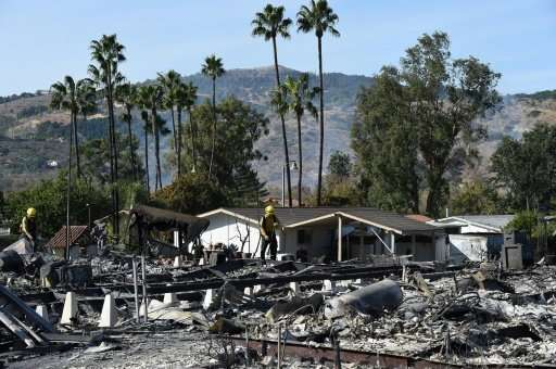 Firefighters comb through smoldering ash in the remains of dozens of homes destroyed by the Lilac Fire in Fallbrook, California