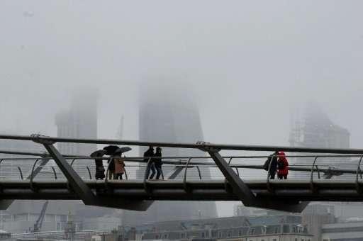 Pedestrians walk over the Millennium Bridge  in central London