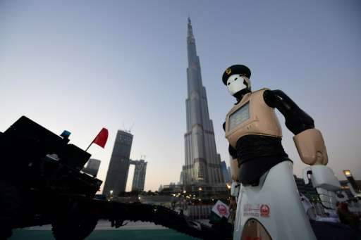 The world's first operational police robot stands to attention in front of Dubai's Burj Khalifa, the tallest tower in the world,