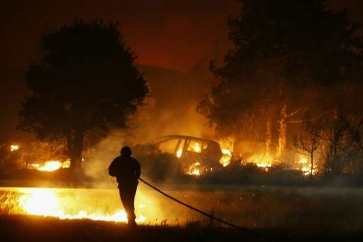 A firefighter battles a blaze in Biguglia, on the French Mediterranean island of Corsica