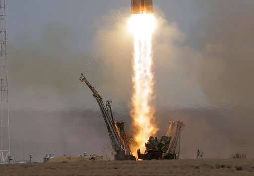 Soyuz space capsule carrying American, Russian blasts off