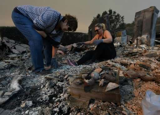 Members of the Reinhardt family sort through the remains of their family home after the Thomas wildfire swept through Ventura, C