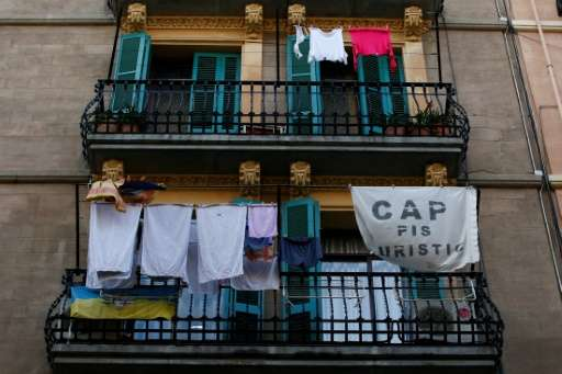 "A banner reading, ""No tourist flats"" hangs from a balcony to protest against holiday rental apartments for tourists in"