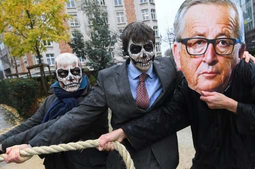 Activists acting as European Commission President Jean-Claude Juncker (R) and Monsanto-characters with their faces painted with