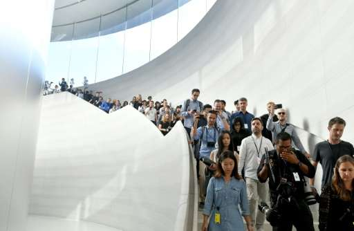 A curved stairway made of gold-toned stone leads down to Steve Jobs Theater built into the hill