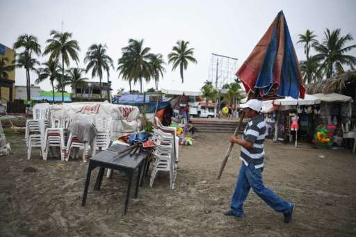 A man carries an umbrella while dismantling his beach business in anticipation of the arrival of Tropical Storm Franklin in the