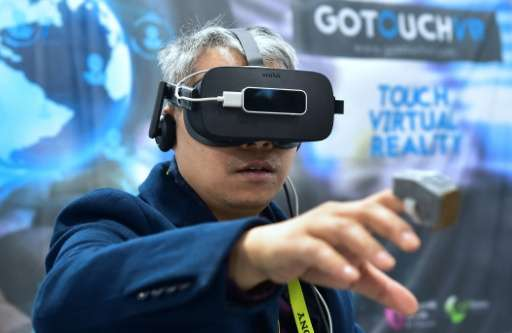A man tries out the VR Touch, a wearable haptic ring creating the illusion of touching virtual objects, at the 2017 Consumer Ele