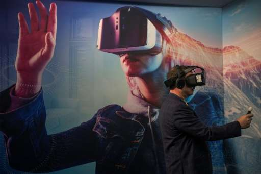 A man wearing a VR headset experiments with a merged reality experience using Project Alloy at the Intel exhibit during the 2017