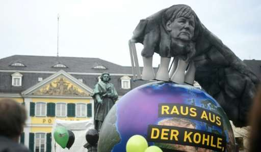 An effigy of Merkel seen in the smoke coming out of a power plant during a demonstration outside climate talks in Bonn