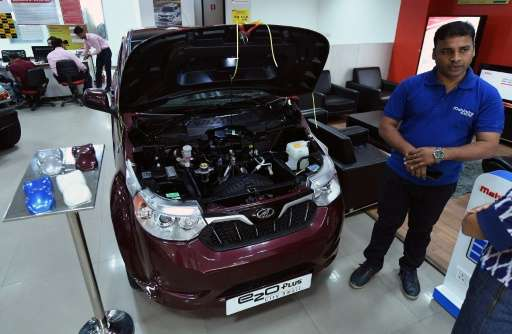 "A sales executive talks about Mahindra's electric car ""e2o Plus"", on display at a showroom in New Delhi"