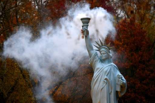 A smoking replica of the Statue of Liberty by Danish artist Jens Galschiot at a park in Bonn during UN climate talks, slowed dow