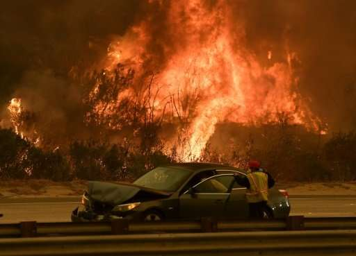 A woman involved in a traffic accident waits to get towed beside a wall of flames on the 101 highway during the Thomas wildfire