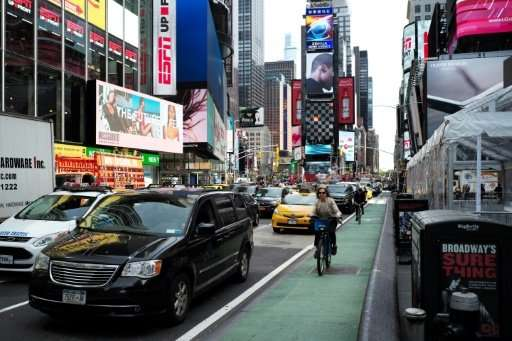 A woman rides in a dedicated bike lane in New York's Times Square
