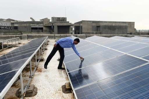 Chinmay Ghoroi, associate professor at the Indian Institute of Technology (IIT) Gandhinagar, next to roof-top solar panels at th