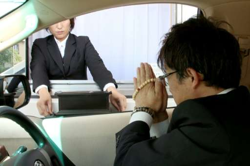 Drive-through mourners can register their names on a touchscreen tablet device and make a traditional offering of incense just b