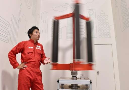 Engineer Atsushi Shimizu, founder and CEO of the Japanese venture company Challenergy, stands next to his bladeless wind turbine