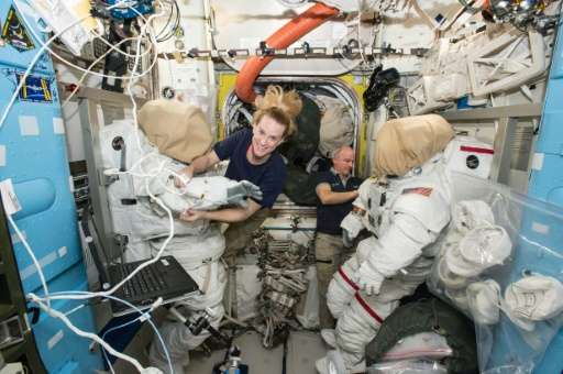 Expedition 48 crew members Kate Rubins and Jeff Williams (R) of NASA outfit spacesuits inside of the Quest airlock aboard the In