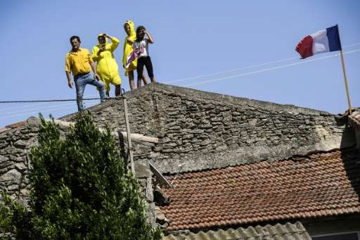 Fans watch the race from the roof of a house during the 165km, 16th stage of the 104th edition of the Tour de France between Le