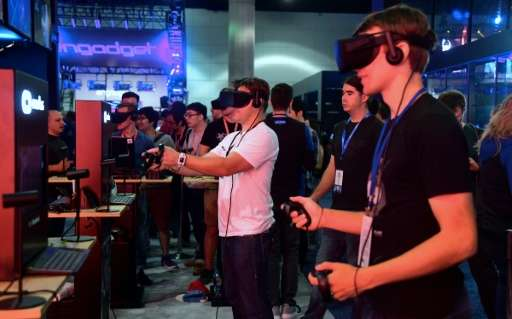 Gaming fans at an electronics show last month in Los Angeles test virtual reality gear of the sort used in a new 'Deadpool' game