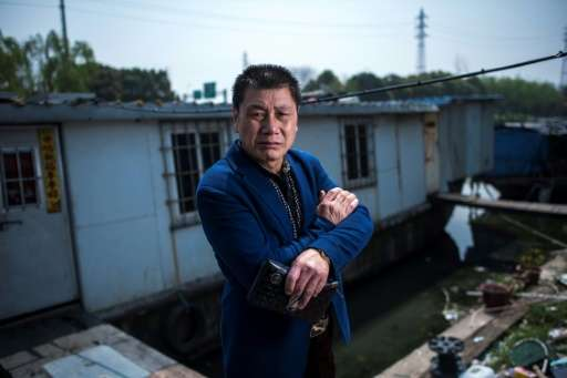 Garbage collector Li Chaoqing faces eviction along with about 200 other squatters living in decaying vessels on the Xinchapu Riv